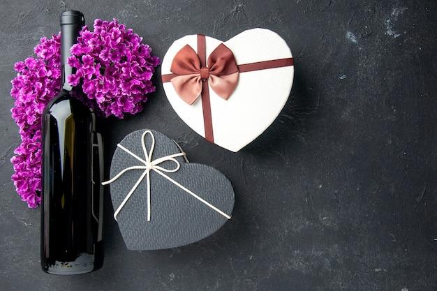 Bovenaanzicht valentijnsdag cadeau met bloemen en fles wijn op donkere achtergrond liefde gevoel paar geschenken kleur alcohol huwelijk