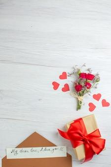 Bovenaanzicht valentijnsdag cadeau met notitie op witte achtergrond gevoel liefde passie minnaar huwelijk hartnoot paar vakantie