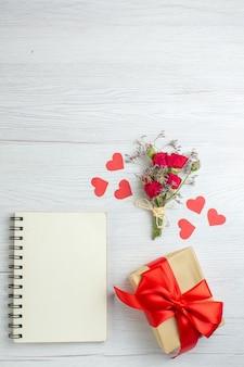 Bovenaanzicht valentijnsdag cadeau met notitieblok op een witte achtergrond gevoel liefde passie minnaar huwelijk hartnoot paar vakantie
