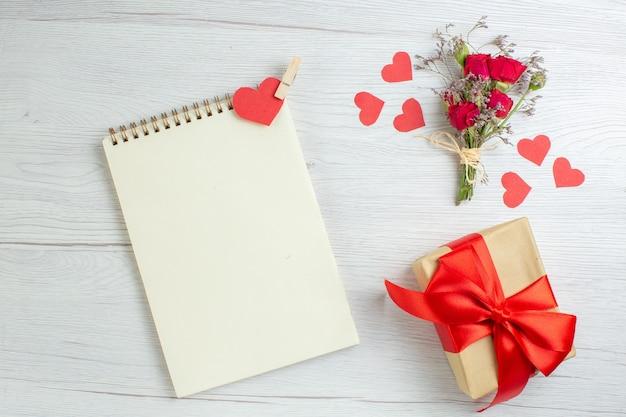 Bovenaanzicht valentijnsdag cadeau met notitieblok op witte achtergrond liefde vakantie passie minnaar paar huwelijk hart gevoel opmerking