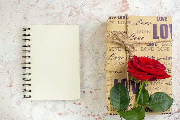 Bovenaanzicht valentijnsdag cadeau met rode roos op lichte achtergrond huwelijk gevoel passie paar liefde minnaar hart kleur