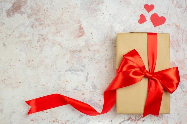 Bovenaanzicht valentijnsdag cadeau met rode strik op lichte achtergrond minnaar liefde paar huwelijk hart kleur gevoel