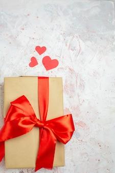 Bovenaanzicht valentijnsdag cadeau met rode strik op lichte achtergrond minnaar liefde paar huwelijk hart kleur gevoelens