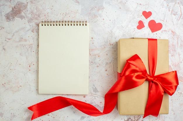 Bovenaanzicht valentijnsdag cadeau met rode strik op lichte achtergrond minnaar liefde paar huwelijk hart kleuren gevoel