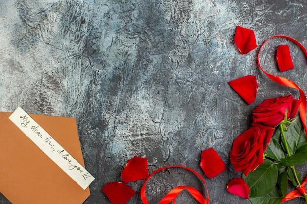 Bovenaanzicht valentijnsdag cadeau rode rozen met notitie lichtgrijze achtergrond paar huwelijk passie liefde vakantie gevoel hart