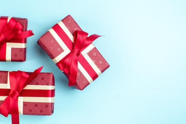 Bovenaanzicht valentijnsdag cadeautjes met rode strik op het blauwe oppervlak paar kleur ik hou van je foto cadeau liefde parfum gevoel