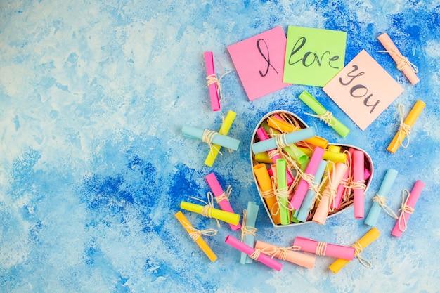 Bovenaanzicht valentijnsdag concept ik hou van je geschreven op plaknotities scroll wenspapieren in hartvormige doos op blauwe achtergrond met kopieerplaats