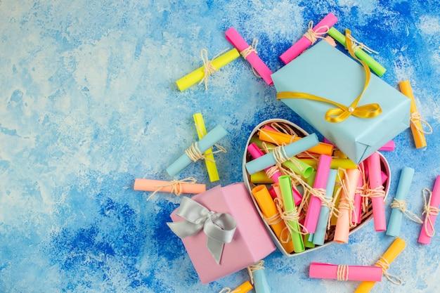 Bovenaanzicht valentijnsdag concept scroll wenspapieren in hartvormige doos geschenken op blauwe achtergrond met kopieerplaats
