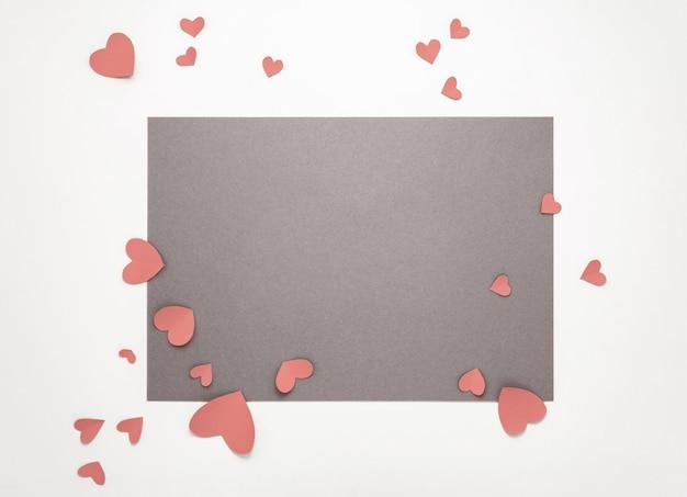 Bovenaanzicht valentijnsdag decoraties plat lag. roze harten op grijze achtergrond. fijne valentijnsdag