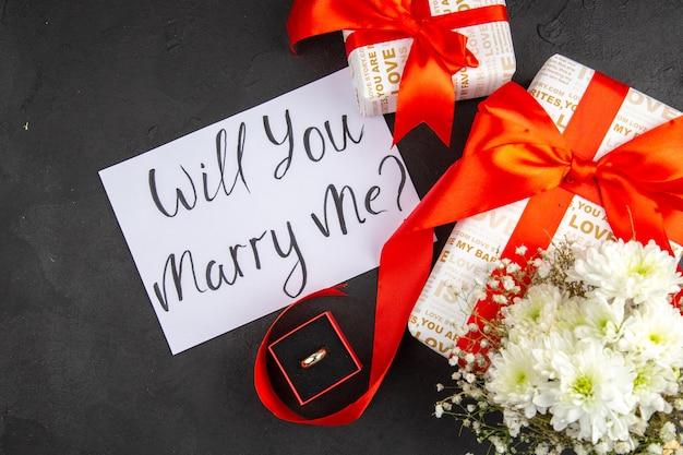 Bovenaanzicht valentijnsdag geschenken bloemen ring in doos wil je met me trouwen geschreven op papier op donkere achtergrond