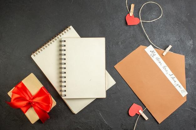 Bovenaanzicht valentijnsdag notitie met cadeau op donkere achtergrond minnaar liefde paar huwelijk hart kleur gevoel