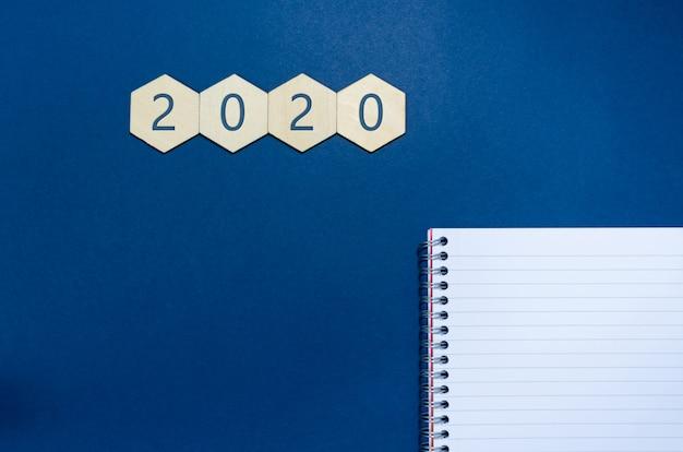 Bovenaanzicht van 2020 geschreven op vier houten zeshoeken met blocnote en pen in een conceptueel beeld voor resolutie van het nieuwe jaar. over blauwe achtergrond met kopie ruimte.