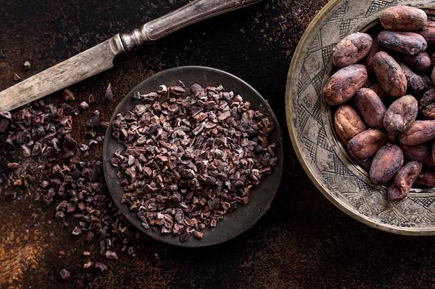 Bovenaanzicht van aan de grond gezette cacaobonen op plaat met mes en cacaobonen