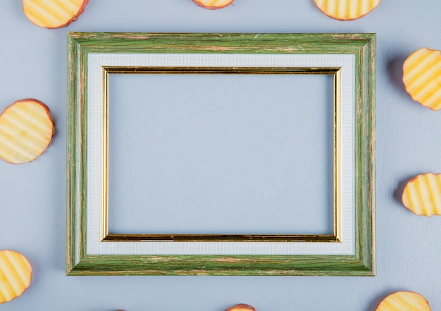 Bovenaanzicht van aardappel segmenten rond frame op blauwe oppervlak met kopie ruimte