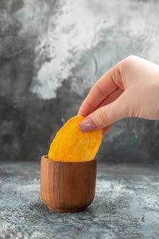 Bovenaanzicht van aardappelchips in een kleine kom ketchup op grijze achtergrond
