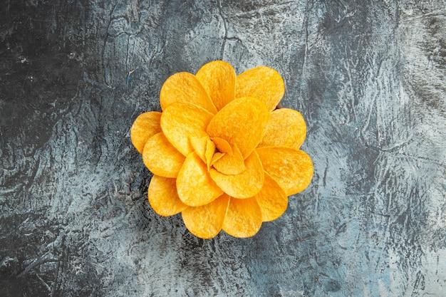 Bovenaanzicht van aardappelchips versierd als bloem gevormd in een bruine kom op grijze tafel