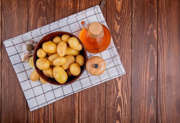 Bovenaanzicht van aardappelen in kom met knoflook citroen zout en boter op geruite doek en hout met kopie ruimte