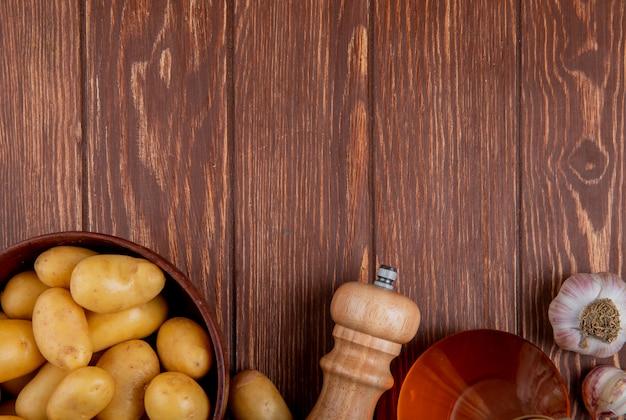 Bovenaanzicht van aardappelen in kom met knoflook zout en boter op hout met kopie ruimte