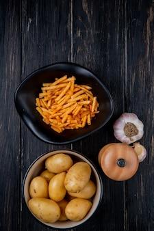 Bovenaanzicht van aardappelen in kommen als gebakken en ongekookt hele met zout en knoflook op hout