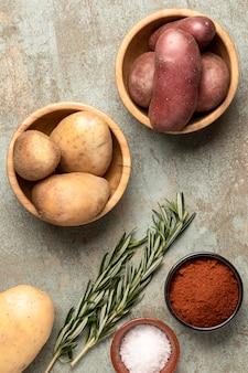 Bovenaanzicht van aardappelen in kommen met kruiden en rozemarijn