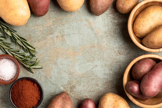 Bovenaanzicht van aardappelen in kommen met rozemarijn en zout
