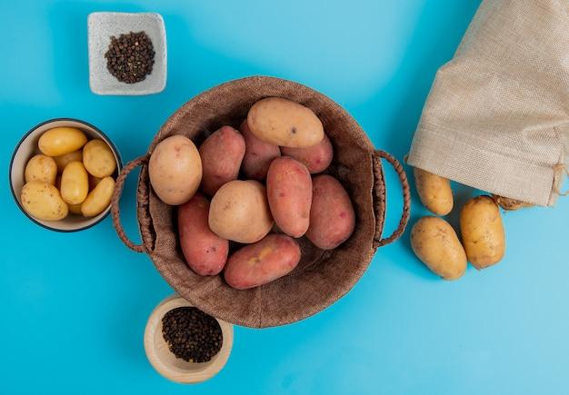 Bovenaanzicht van aardappelen in mand en in kom met andere morsen uit zak en zwarte peper zaden op blauwe oppervlak