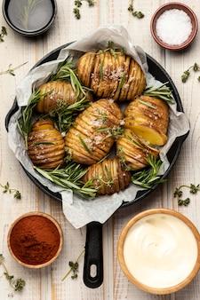 Bovenaanzicht van aardappelen in pan met rozemarijn en specerijen