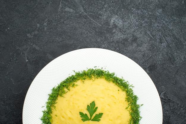 Bovenaanzicht van aardappelpuree met greens binnen plaat op grijs
