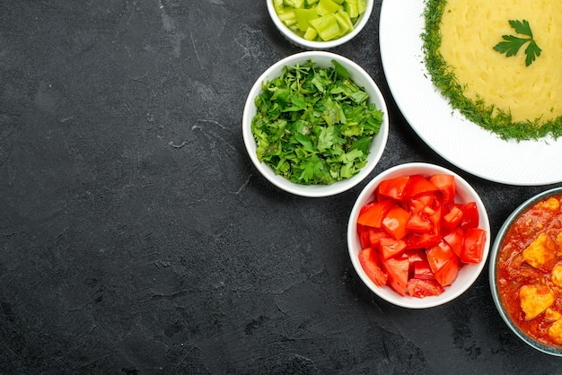Bovenaanzicht van aardappelpuree met greens en gesneden tomaten op grijs