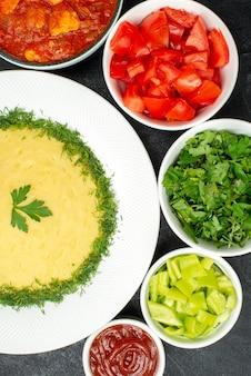 Bovenaanzicht van aardappelpuree met groenten en gesneden tomaten op donkergrijs