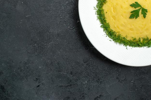 Bovenaanzicht van aardappelpuree met groenten in plaat op grijze vloer
