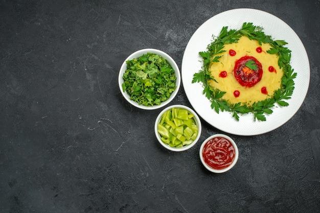 Bovenaanzicht van aardappelpuree met tomatensaus en greens op dark