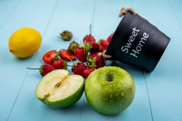 Bovenaanzicht van aardbei die uit een mand met groene appels met citroen op een blauwe achtergrond valt