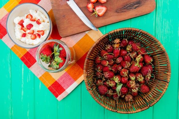 Bovenaanzicht van aardbeien in de mand met kommen kwark en aardbeien op doek op groene ondergrond