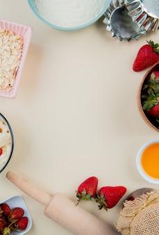 Bovenaanzicht van aardbeien in kom en gesmolten boter met bloem en haver met deegroller op wit oppervlak met kopie ruimte