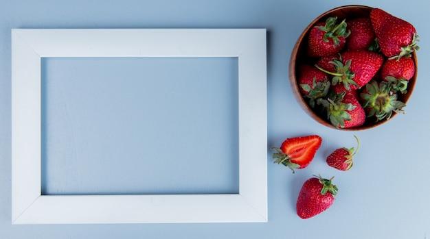 Bovenaanzicht van aardbeien in kom en wit frame op blauwe oppervlak met kopie ruimte