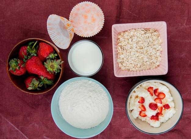 Bovenaanzicht van aardbeien in kom met kwark melk melk haver op bordo doek oppervlak
