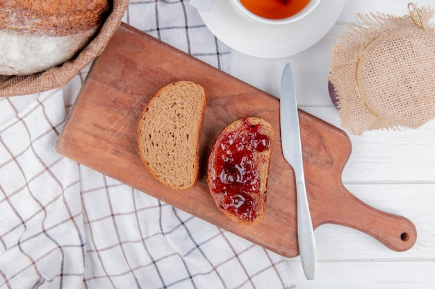 Bovenaanzicht van aardbeienjam besmeurd met gesneden roggebrood met mes op snijplank en cob op geruite doek met thee en jam op houten tafel