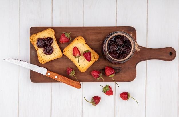 Bovenaanzicht van aardbeienjam op een houten keukenbord met mes met verse aardbeien op een witte houten achtergrond