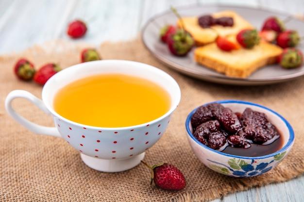 Bovenaanzicht van aardbeienjam op een kom met een kopje thee op een zakdoek op een grijze houten achtergrond