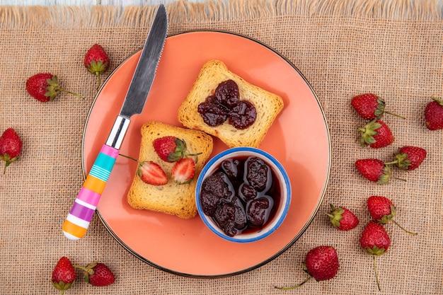 Bovenaanzicht van aardbeienjam op een kom met geroosterd brood met mes op zak doek achtergrond