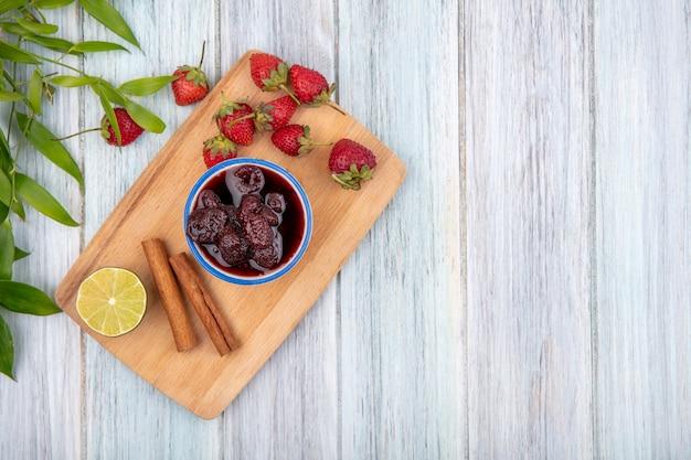 Bovenaanzicht van aardbeienjam op een kom op een houten keukenbord met kaneelstokjes op een grijze houten achtergrond met kopie ruimte