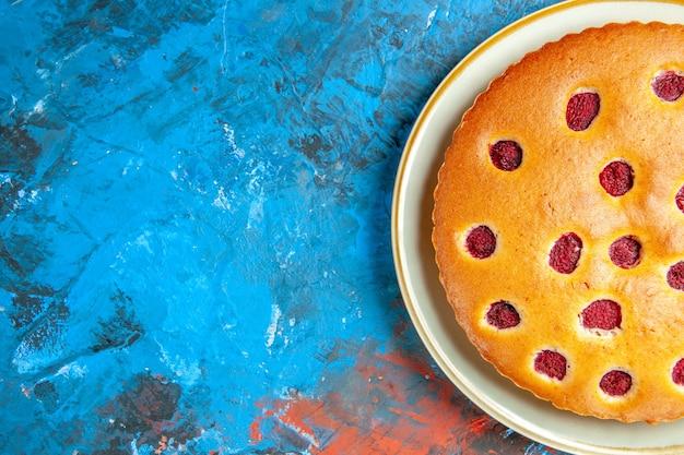 Bovenaanzicht van aardbeientaart op witte ovale plaat op blauwe ondergrond