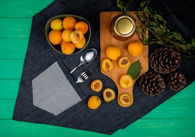 Bovenaanzicht van abrikozen en perzik jam op snijplank met kom van abrikozen dennenappels bladeren op jeans doek met lepel en vork in zak op groene achtergrond