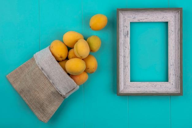 Bovenaanzicht van abrikozen in een jutezak met een grijs frame op een blauw oppervlak