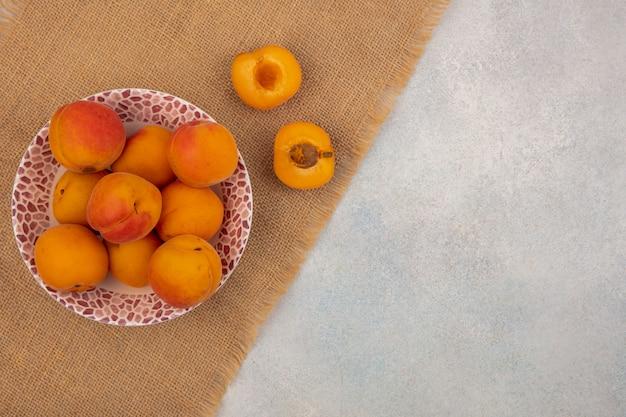 Bovenaanzicht van abrikozen in kom en de helft gesneden op zak op witte achtergrond met kopie ruimte
