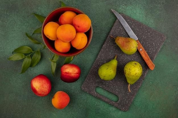 Bovenaanzicht van abrikozen in kom met patroon van perziken peren met mes en bladeren op snijplank en op groene achtergrond