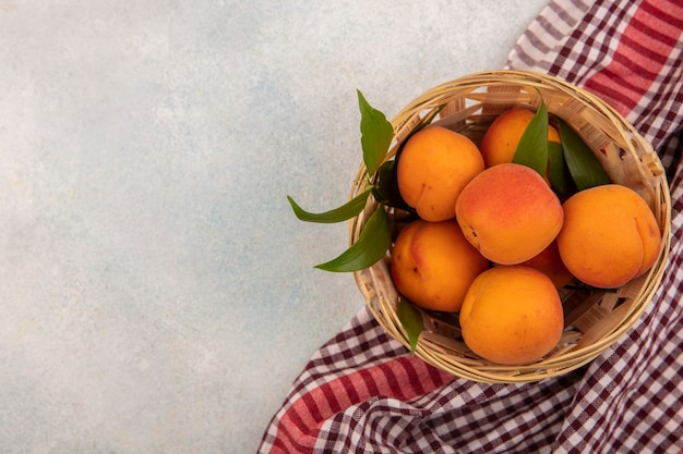 Bovenaanzicht van abrikozen in mand op geruite doek en witte achtergrond met kopie ruimte