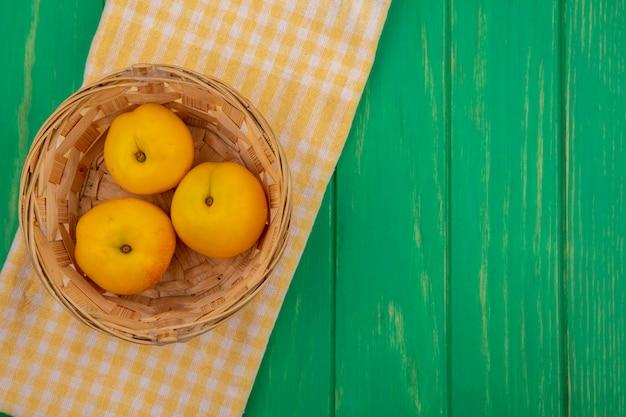 Bovenaanzicht van abrikozen in mand op geruite doek op groene achtergrond met kopie ruimte