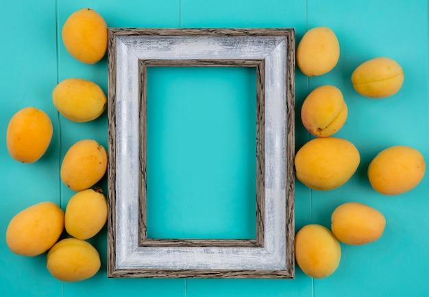Bovenaanzicht van abrikozen met grijs frame op een blauwe ondergrond